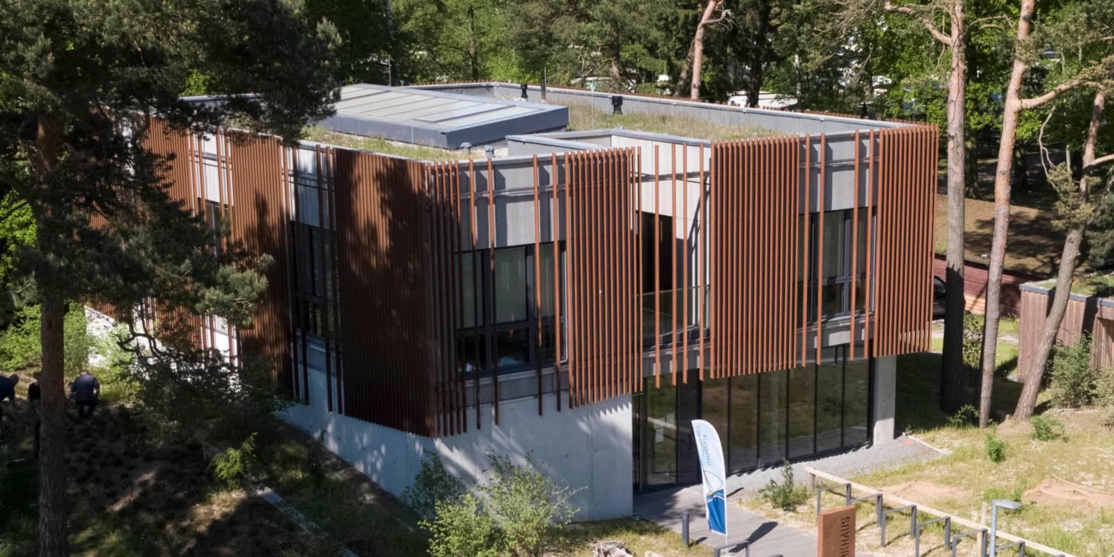 Vogelperspektive: Neubau mit besonderer Fassade aus Metallelementen. Das Gebäude ist eingebettet in die umgebende Dünenlandschaft und liegt direkt am Steinhuder Meer Rundweg.