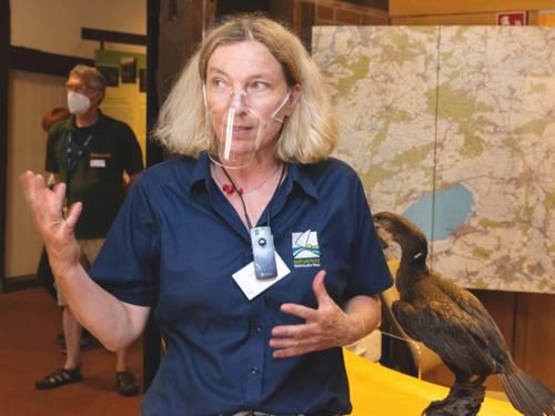 Eine Frau trägt ein Poloshirt mit dem Naturparklogo und erklärt etwas, ihre Hände sind zu einer Geste ausgestreckt.