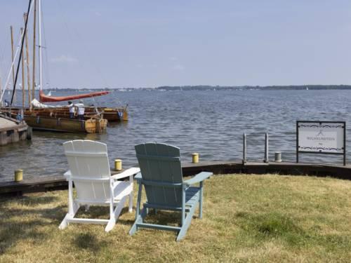 Ein weißer und ein blauer Holzstuhl am Ufer, Blick auf das Steinhuder Meer
