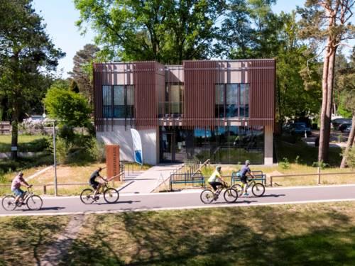 Radfahrerinnen und Radfahrer fahren auf dem Steinhuder Meer Rundweg und kommen direkt am Naturparkhaus in Mardorf vorbei.