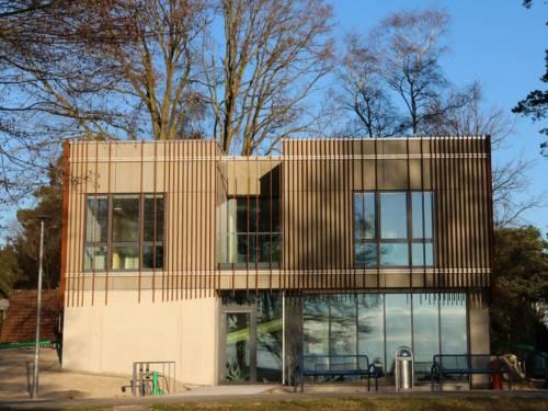 Modernes Gebäude mit flachem Dach und einer Fassade mit Metallstreben.