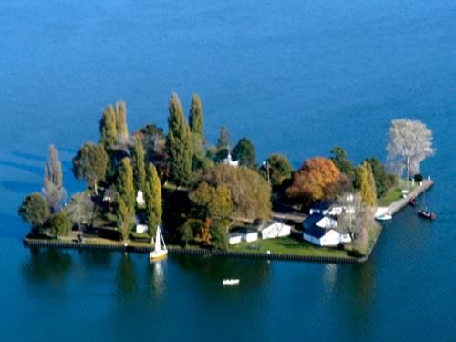 Luftaufnahme: Nahezu quadratische, flache Insel mit Bäumen und Gebäuden. Am Ufer ankern zwei Segelbote.