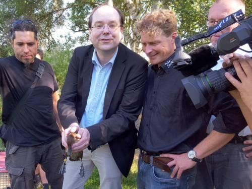 Vier Männer und die Hände eines Kameramanns sind zu sehen. Die zweite Person von links hält eine Moorente.
