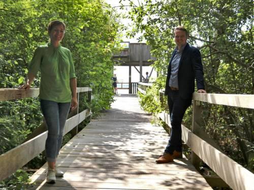 Eine Frau und ein Mann stehen versetzt auf einem Holzsteg, im Hintergrund ist ein Aussichtsturm zu sehen.