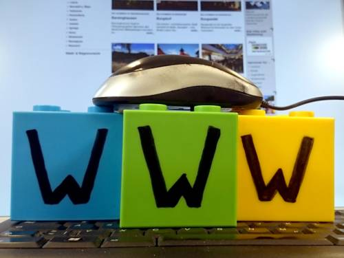 """Eine Maus liegt auf drei Plastikbausteinen, diese wiederum stehen auf einer Tastatur, dahinter zeigt ein Bildschirm eine Webseite an. Auf jedem der drei Bausteine steht der Buchstabe """"W""""."""