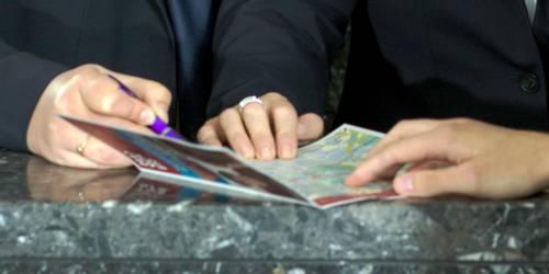 Eine Broschüre liegt auf einem Tresen, die Hände mehrerer Personen berühren die aufgeschlagenen Seiten.