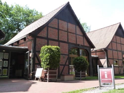 Fachwerkgebäude im Scheunenviertel Steinhude, davor steht ein Aufsteller aus Metall, der auf die Tourist Information Steinhude verweist.