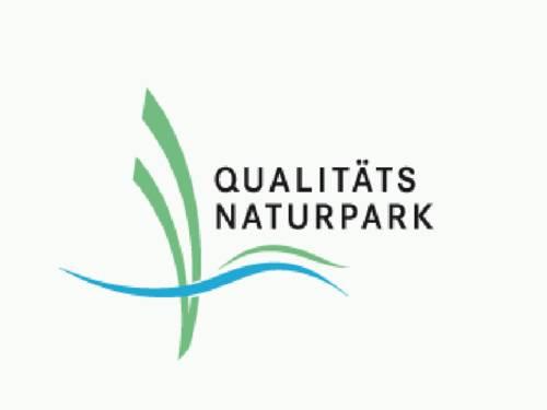 """Logo mit Linien in den Farben Grün und Blau und der Text """"Qualitäts Naturpark""""."""