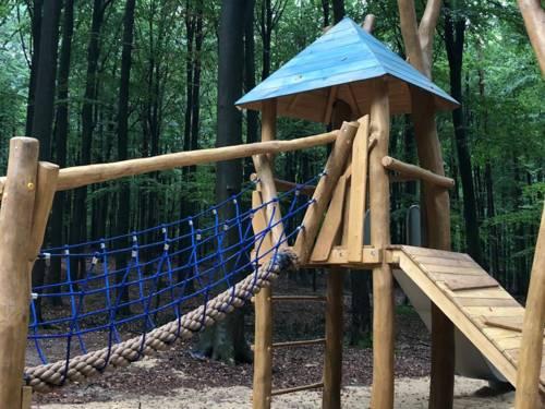 Kletterturm auf einem Spielplatz in einem Wald.