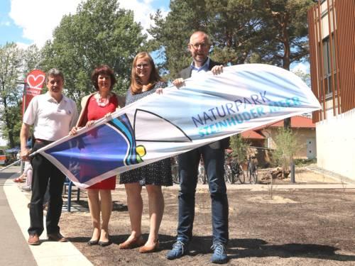 Zwei Männer und eine Frau stehen neben dem Naturparkhaus in Mardorf und halten eine Strandflagge, auf der das Logo des Naturparks Steinhuder Meer abgebildet ist.