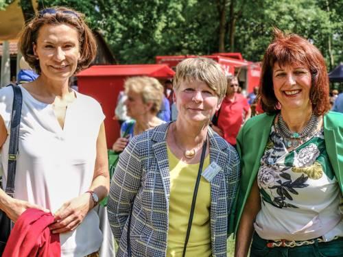 Drei Frauen stehen nebeneinander, dahinter wird ein Fest gefeiert.