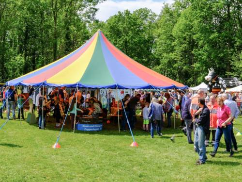 Ein Zirkuszelt steht auf einer grünen Wiese, die Seiten sind offen, so dass aus allen Richtungen Menschen hinein und heraus spazieren können. Auf dem Platz herrscht insgesamt buntes Treiben.