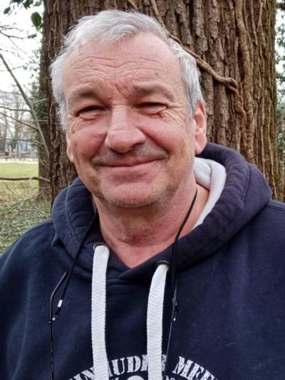 Portraitfoto eines Mannes vor einem Baum.