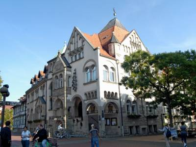 Mehrgeschossiges Gebäude mit Rundbogenfenstern, mehreren Spitzdächern und einem Glockenspiel an der Außenfassade.