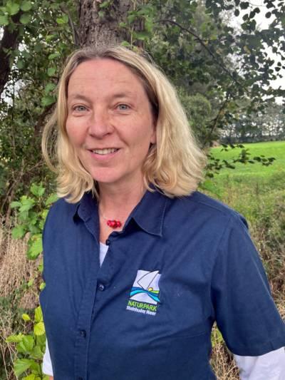 Porträtfoto einer Frau in einem blauen Poloshirt mit Naturparklogo.