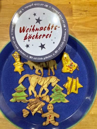 """Kekse liegen auf einem Teller, dazu ein runder Dosendeckel mit der Aufschrift """"Weihnachtsbäckerei""""."""