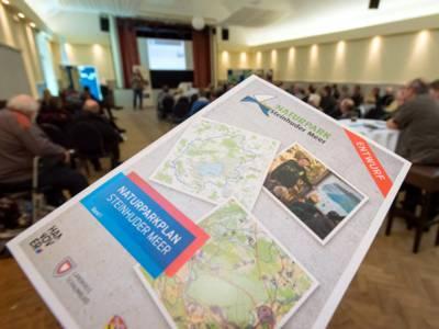 Der Entwurf des Naturparkplans im Vordergrund, im Hintergrund ein Veranstaltungssaal.