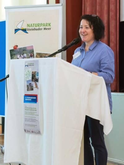 Eine Frau steht an einem Rednerpult und spricht in ein Mikrofon.