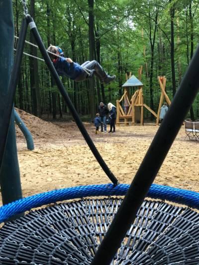 Schaukelgeräte auf einem Spielplatz in einem Wald.
