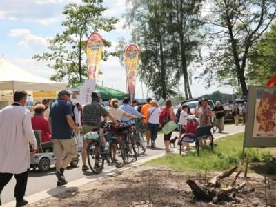Menschen gehen eine Straße entlang und schauen auf die Ausstellenden am Weg, einige schieben dabei Fahrräder.