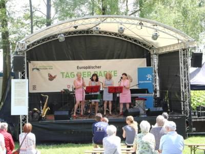 Vier Frauen stehen auf einer Bühne, Publikum verfolgt das Geschehen.