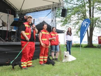Vier Menschen und drei Hunde stehen vor einer Bühne.