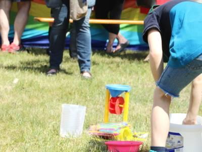 Ein Kind spiel mit Gartenspielzeug auf einer Wiese.