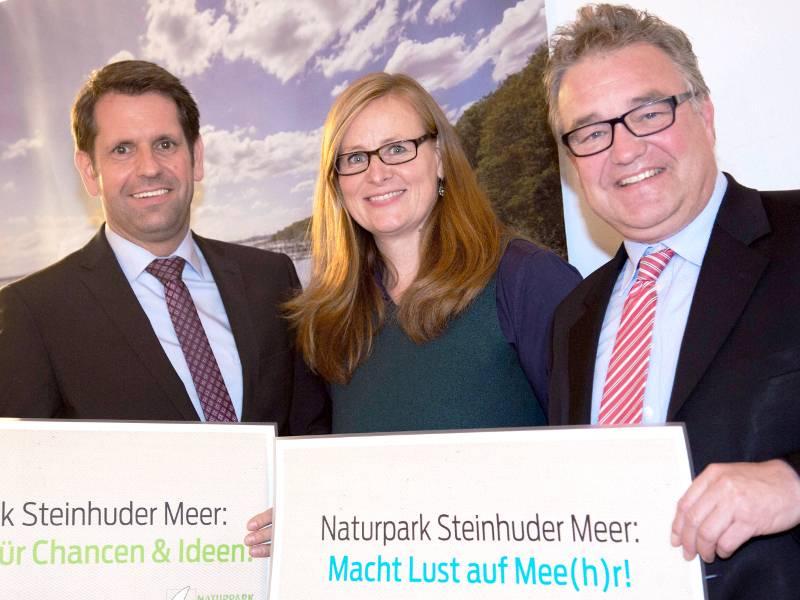 """Zwei Männer und eine Frau stehen nebeneinander, sie halten halten Karten mit Aufschriften wie zum Beispiel """"Naturpark Steinhuder Meer: Macht Lust auf Mee(h)r!""""."""