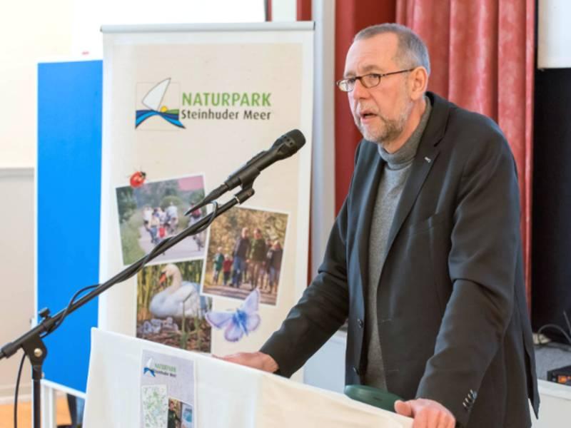 Ein Mann steht an einem Rednerpult, daneben ist ein Rollup-Display mit dem Logo des Naturparks Steinhuder Meer.