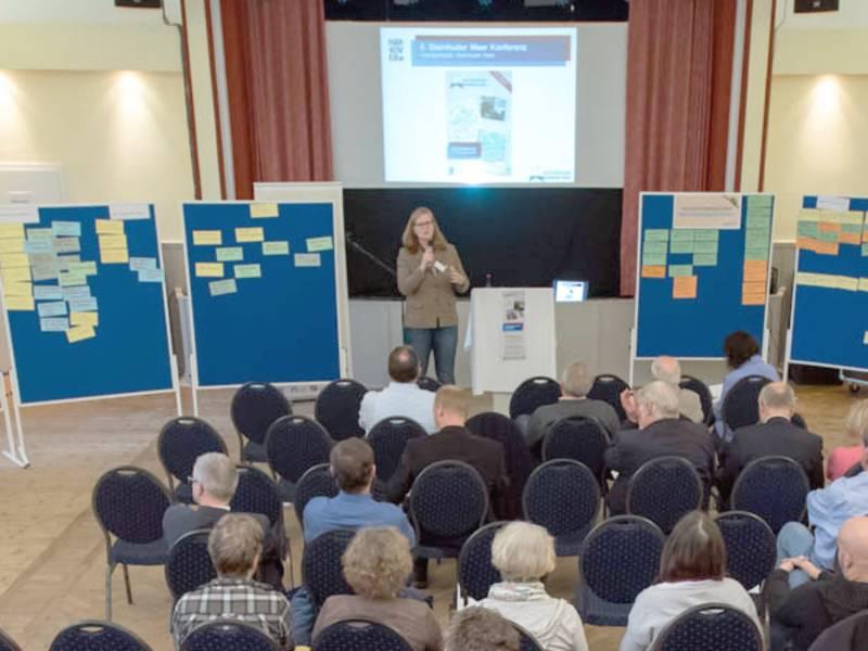 Eine Frau spricht vor Publikum.