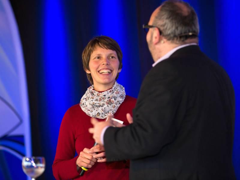 Ein Mann und eine Frau stehen auf einer Bühne und sprechen vor Publikum.