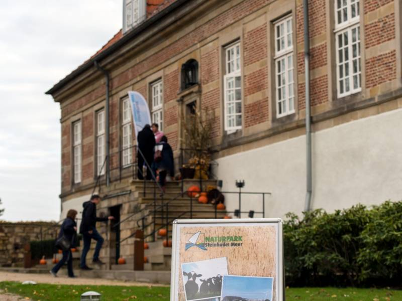 Menschen betreten Schloss Landestrost über eine Treppe, im Vordergrund informiert ein Display über die Steinhuder Meer Konferenz 2017.