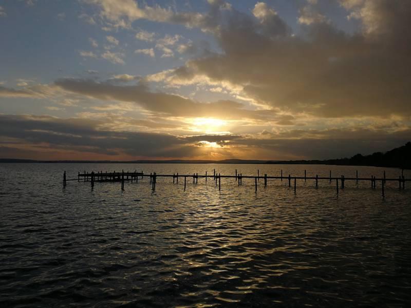 Die Sonne scheint am Steinhuder Meer durch einen wolkigen, dämmerigen Himmel.