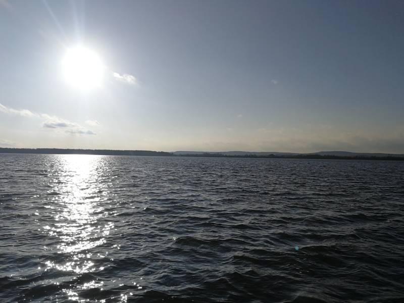 Die Sonne scheint am Steinhuder Meer durch einen sonnigen Himmel.