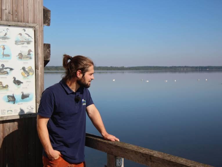 Ein Mann steht an dem Geländer eines Aussichtsturms. Er trägt ein blaues Poloshirt mit dem Logo des Naturparks Steinhuder Meer.