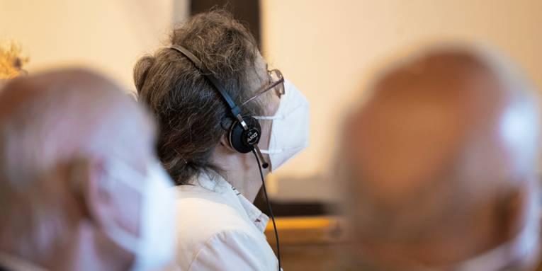 Eine Frau trägt Kopfhörer und eine FFP2-Maske. Sie folgt einem Vortrag. Verschwommen sind weitere Besucher zu erahnen.