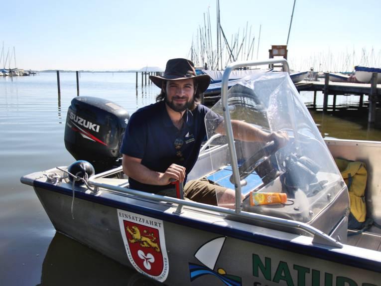 """Naturparkranger Milan Mato Glatt sitzt in dem Boot """"Wasserläufer"""", es ist an einem Steg festgemacht."""