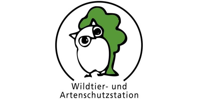 """Logo: Eine mit wenigen Strichen gezeichnete Eule steht vor einem gezeichneten Baum. Ein nach unten offener Kreisbogen umschließt die Zeichnungen. In der Öffnung unten steht: """"Wildtier- und Artenschutzstation""""."""