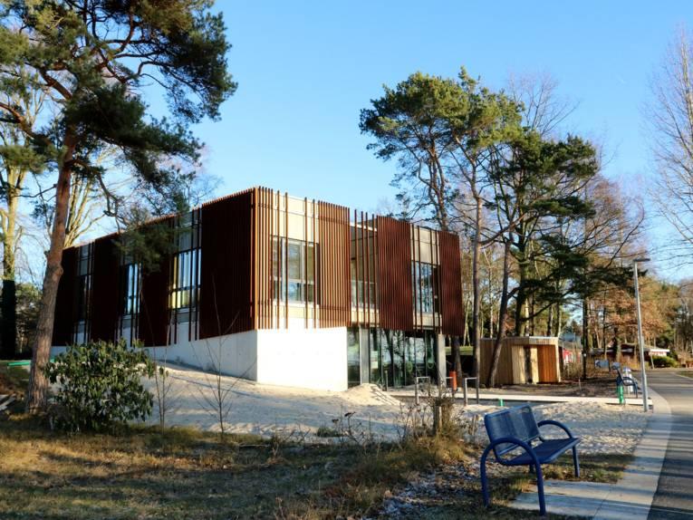 Neubau mit besonderer Fassade aus Metallelementen. Das Gebäude ist eingebettet in die umgebende Dünenlandschaft.