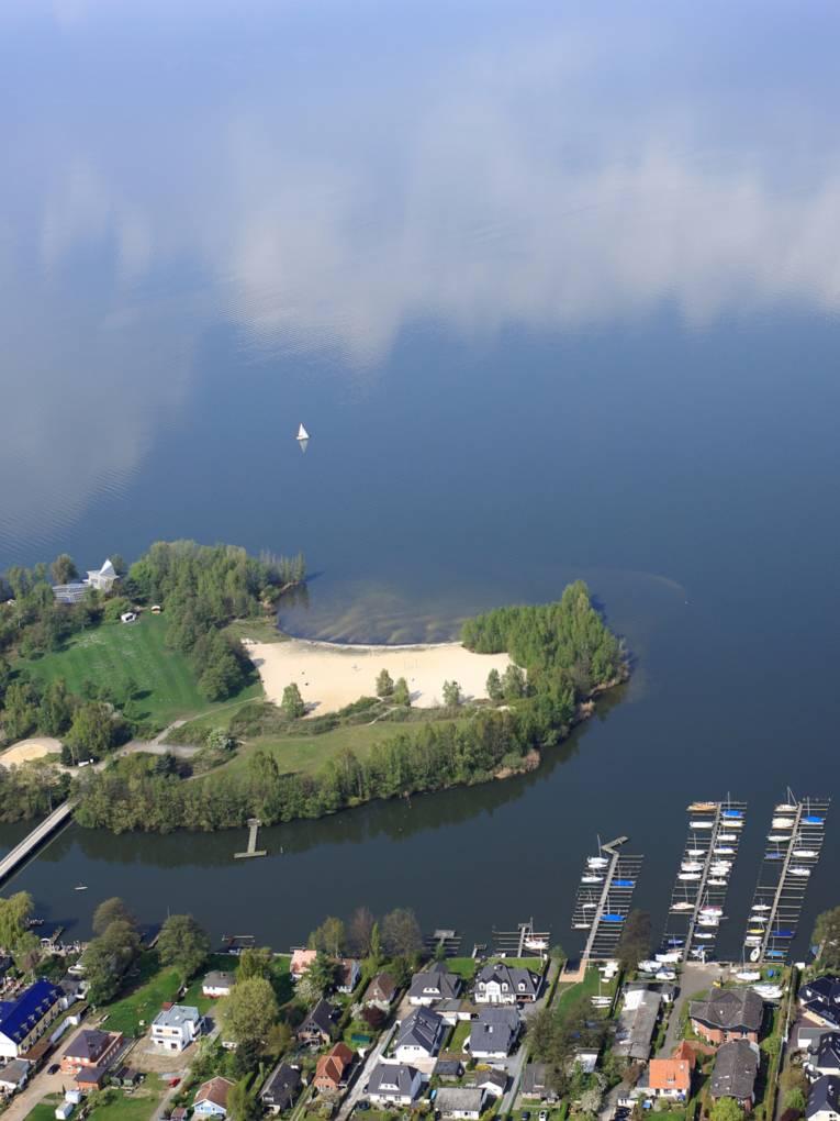 Blick aus einem Flugzeug auf das Ufer des Steinhuder Meeres mit Bootsanlegern und Wald und der Badeinsel.
