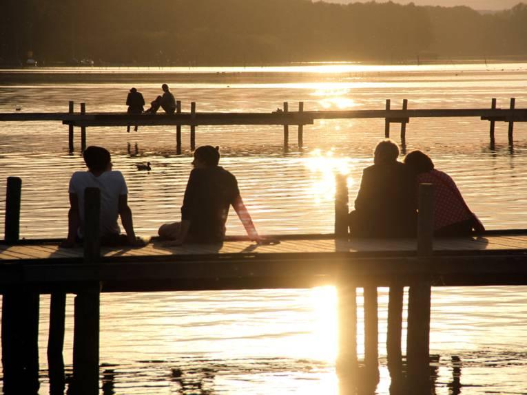 Zwei Steege ragen ins Steinhuder Meer, darauf sitzen sechs Menschen während die Sonne untergeht.
