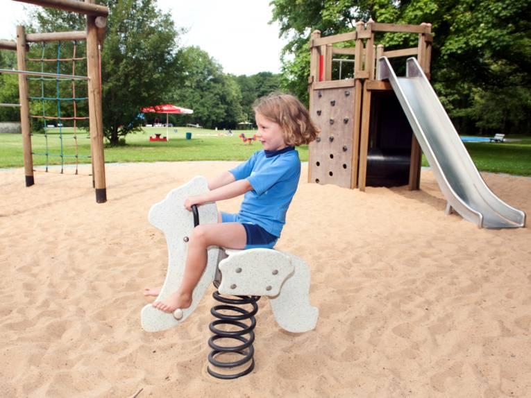 Ein Kind reitet auf einem Schaukelpferd, im Hintergrund sind eine Rutsche und ein Klettergerüst.