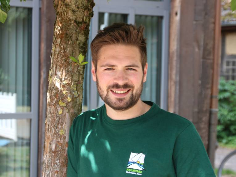 Porträt eines Mannes, er trägt ein grünes T-Shirt mit dem Logo des Naturparks Steinhuder Meer.