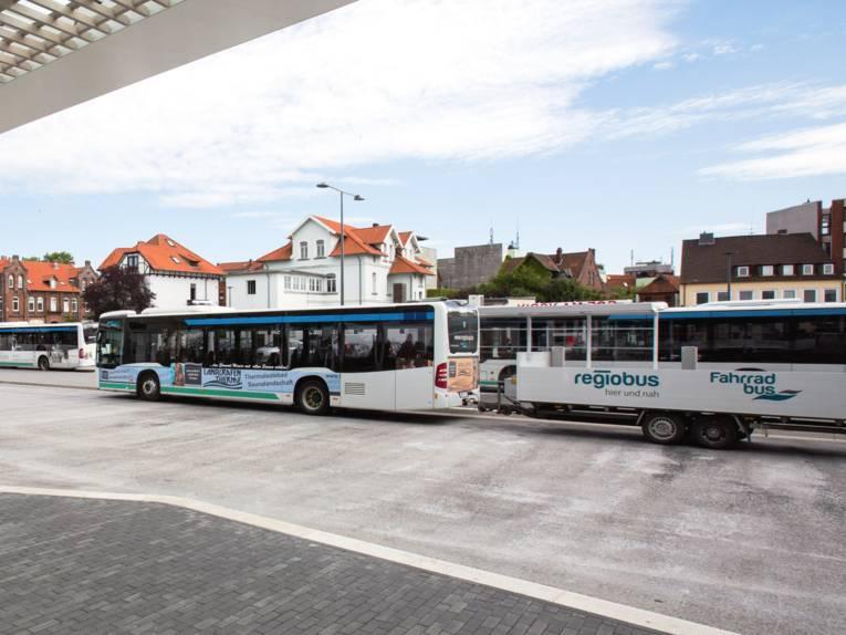 Hinter einem Linienbus hängt ein Anhänger.