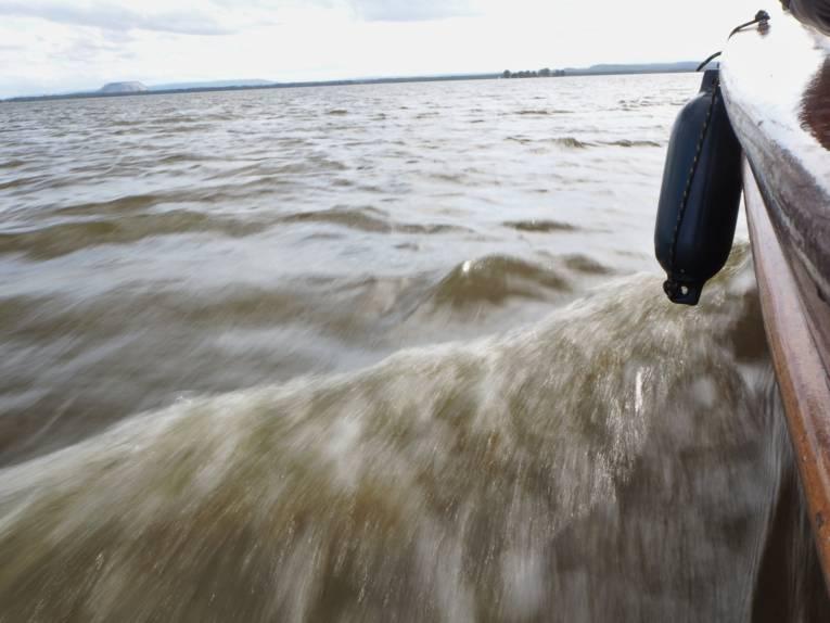 Ein Boot schiebt eine kleine Bugwelle vor sich her.