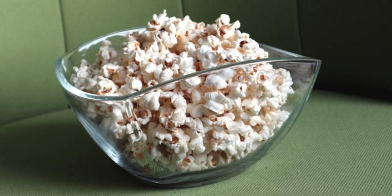 Popcorn in einer Glasschüssel auf einem grünen Sessel.