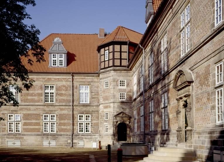 Auf dem Gelände des Neustädter Schloss Landestrost: Ein Teil des Gebäudes, der Eingangsbereich mit Treppe und links im Bild ein Teil einer Baumkrone sind zu sehen.
