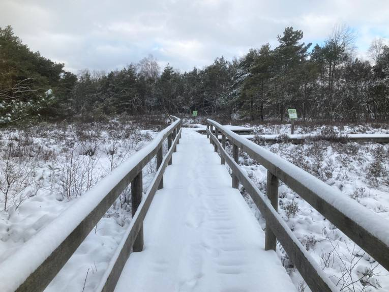 Eine dicke Schneeschicht liegt auf dem Steg.