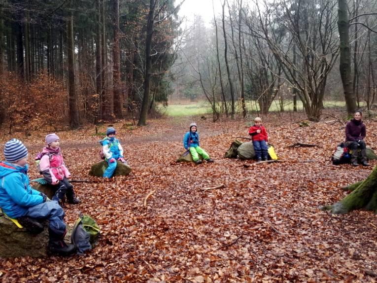 Fünf Kinder und eine Frau sitzen auf Findlingen, sie bilden dabei einen Halbkreis.