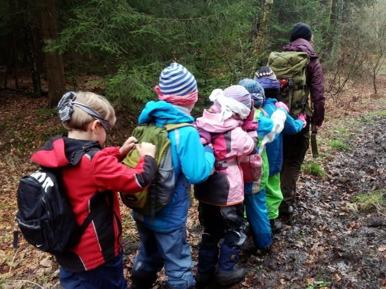 Fünf Kinder laufen mit verbundenen Augen hintereinander her und halten sich beim jeweils vorderen Kind am Rucksack fest. Allen voran geht eine Frau als sechste Person, an ihrem Rucksack hält sich das erste Kind fest.
